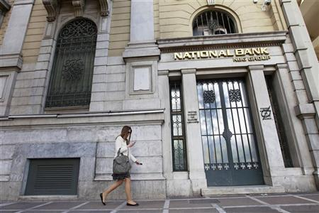 A woman walks outside a National Bank of Greece branch in central Athens April 20, 2012. REUTERS/John Kolesidis